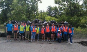Group pic in front of dumpster HYPE professionals filled with trash.